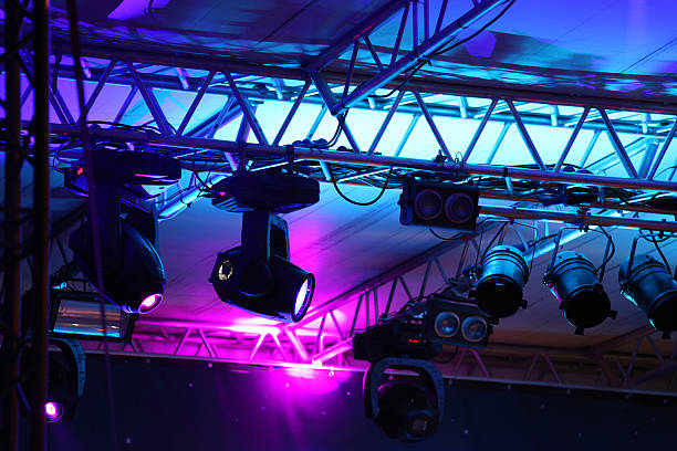 Stage lights flooding a theather at an entertainment event, with blue and purple light beams, lighting equipments and steel structures.