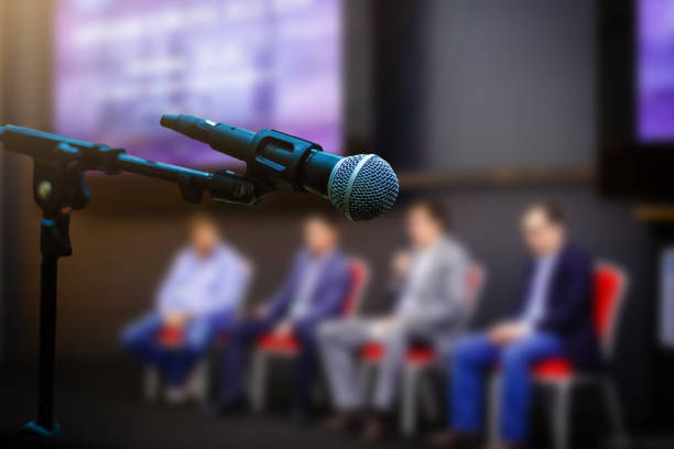 Microphone in front businesspeople blurred in conference meeting room