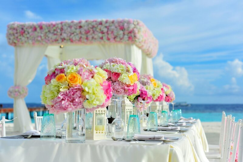 Flowers in vases on a table on the beach.