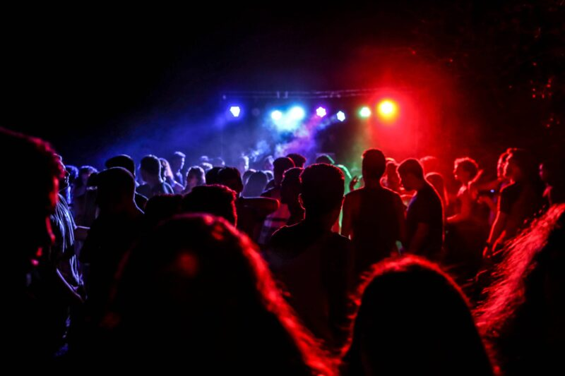 People inside a music venue with limited lighting/