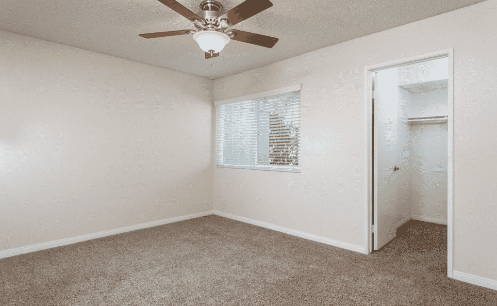 Empty Bedroom with ceiling fan and carpet