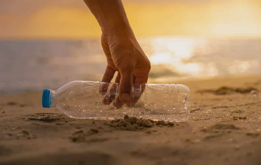 a hand picking up an empty plastic bottle on the beach