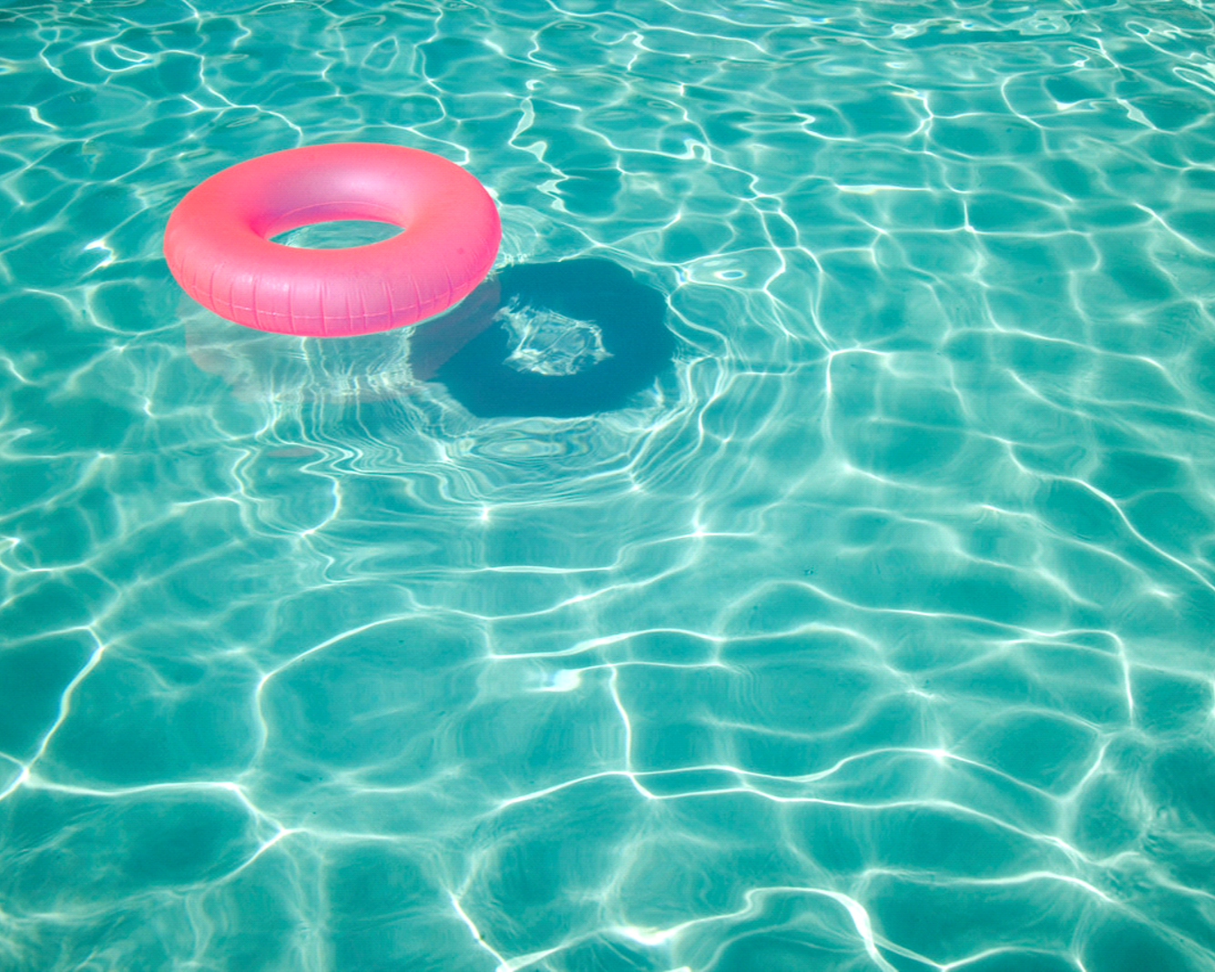 Pink inflatable tube floating in pool water