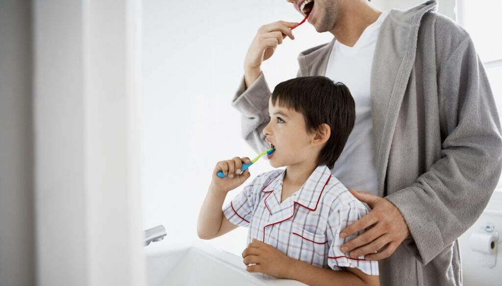 son and father brushing teeth