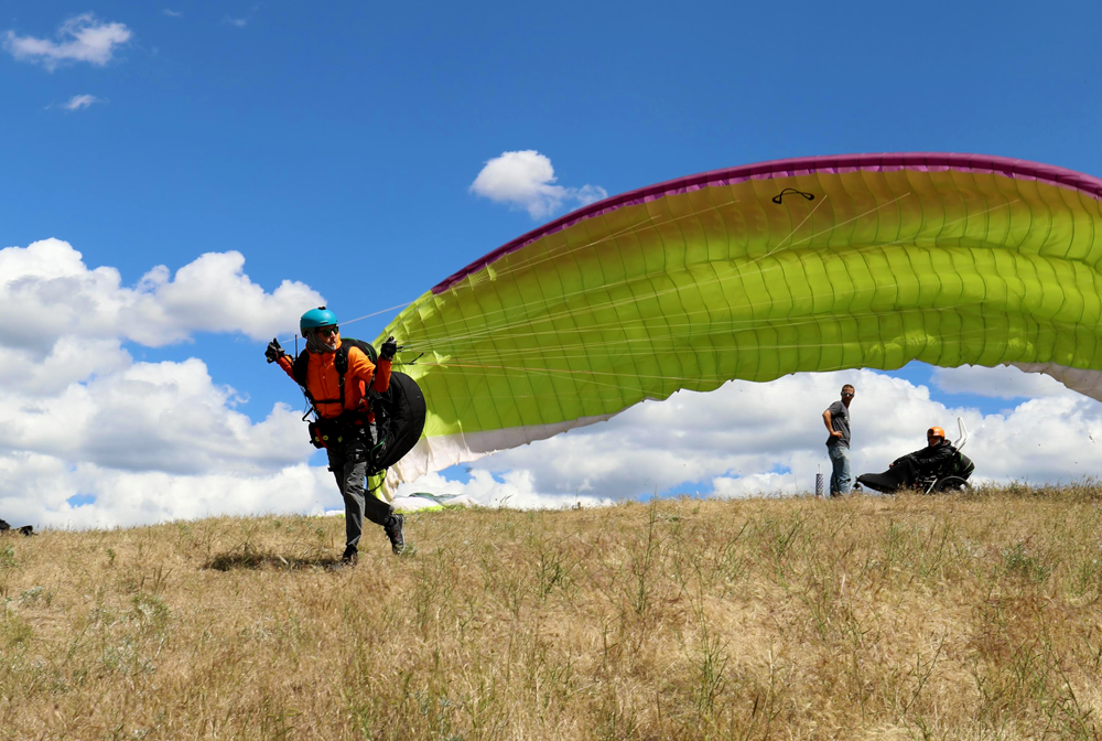 A paraglider running off launch after training.