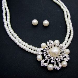 necklace and earrings with pearls arranged in floral patterns