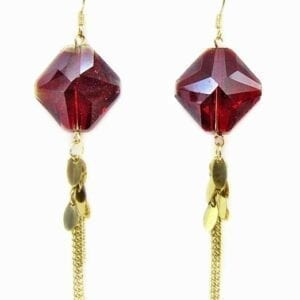 close up of earrings with red gem and tassel