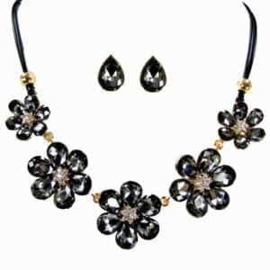 necklace and earrings with dark crystals arranged in flowers