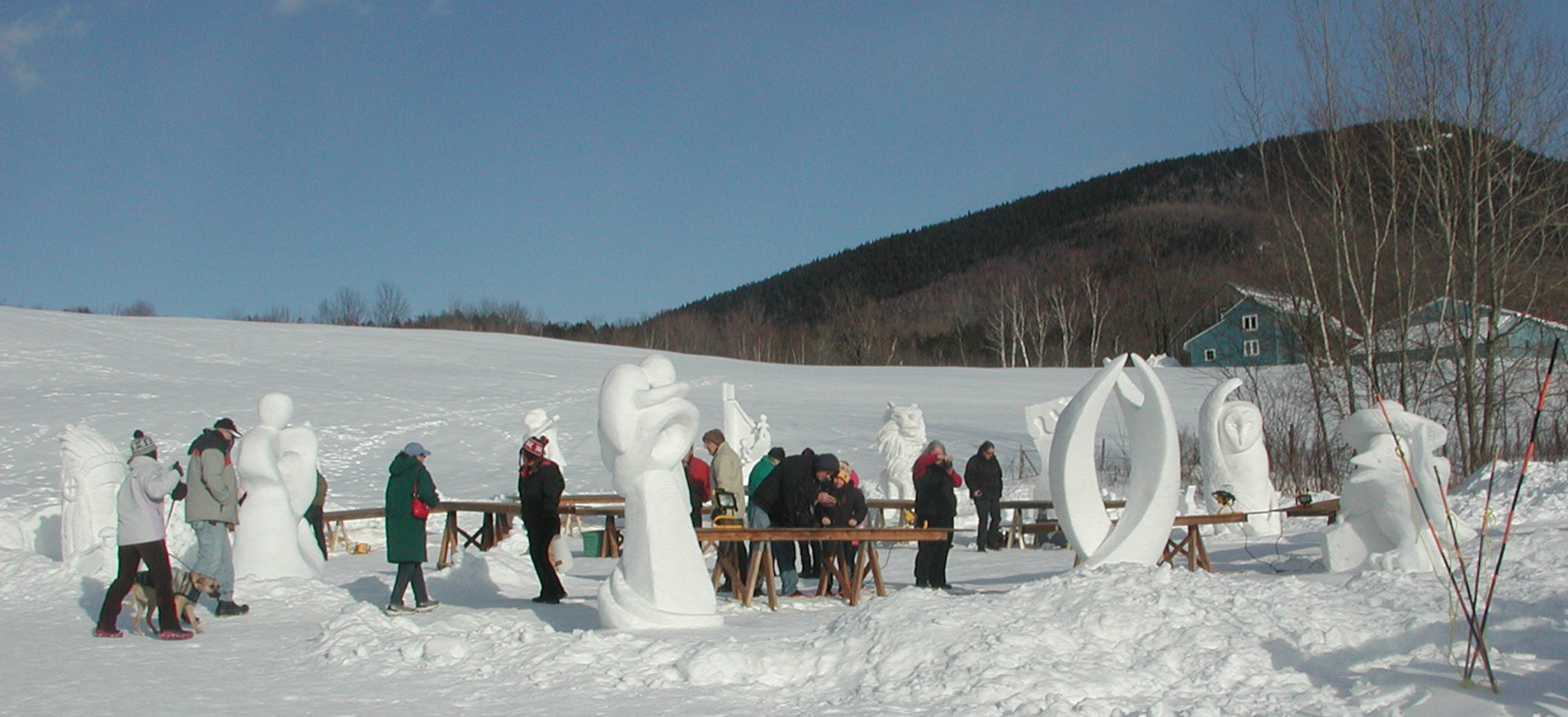 snow sculptors working on sculptures with mountain in background