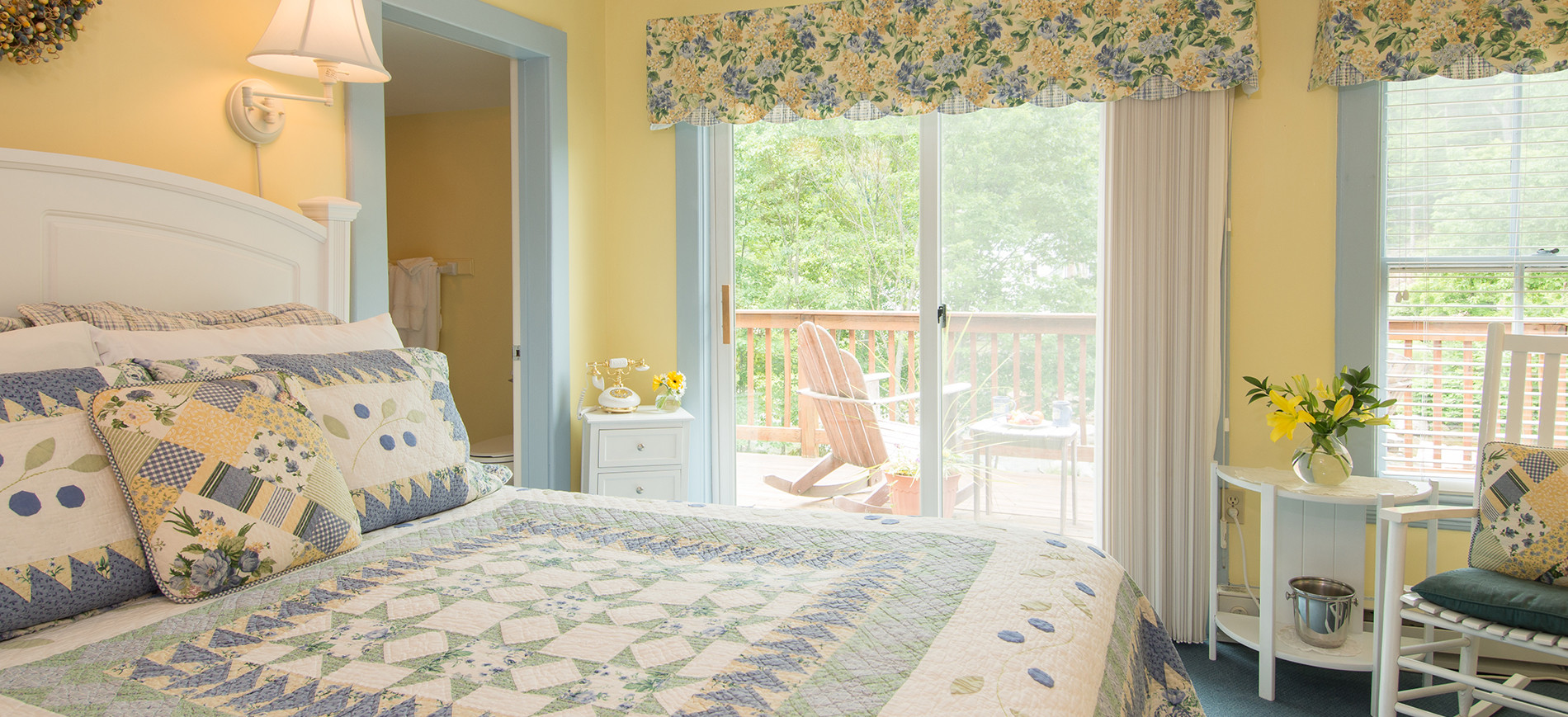 Guest room with yellow walls, queen bed with white, yellow, blue bedding, sliding glass door with Adirondack chairs on balcony, white table, white rocker