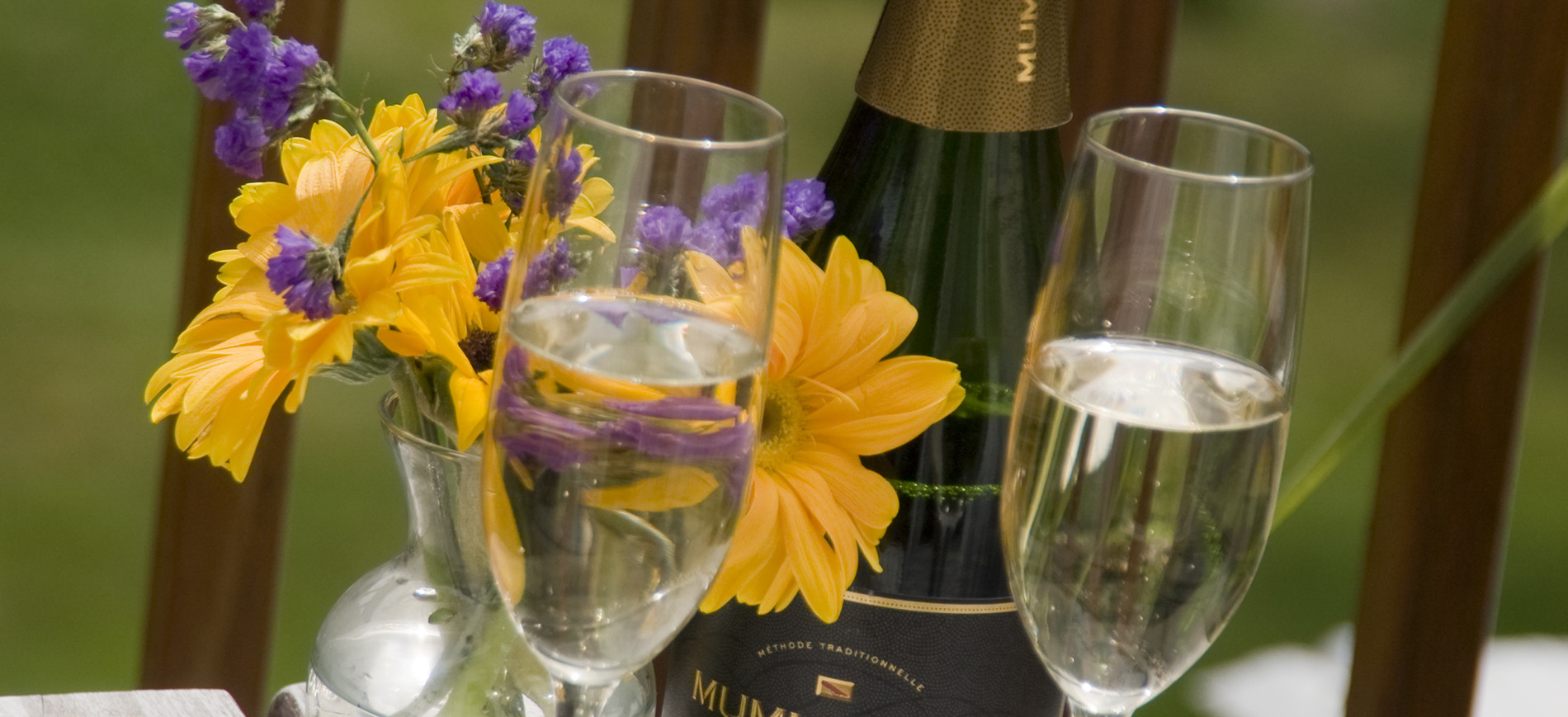 champagne glasses in front of vase of yellow and purple flowers and champagne bottle