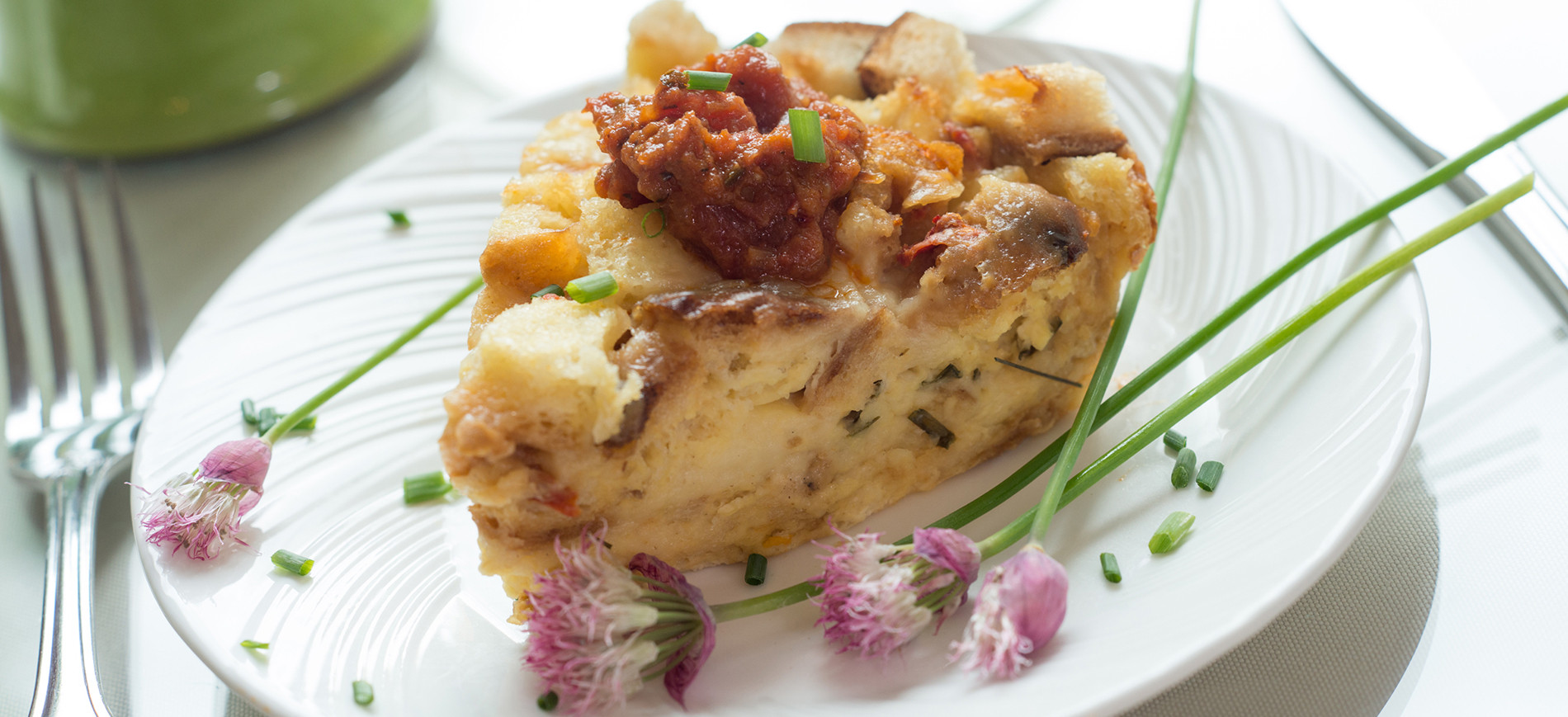 Chive and cheddar strata on white plate with chive blossom garnish