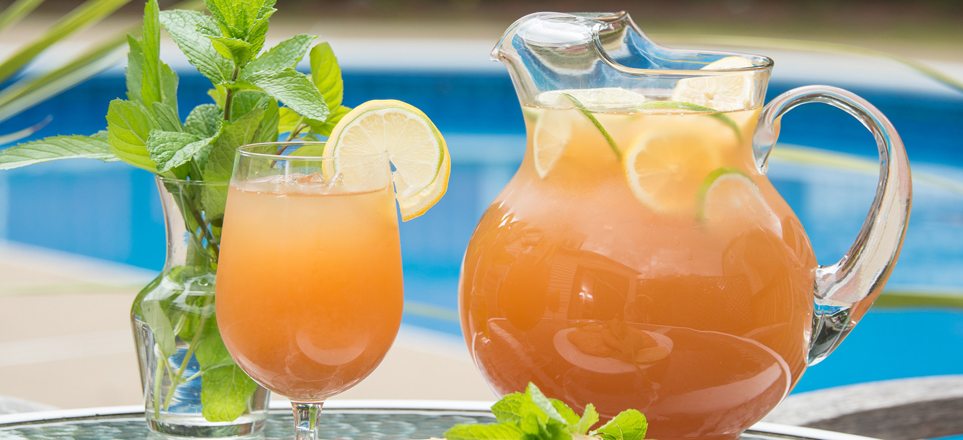Iced tea pitcher and glass with pool in background