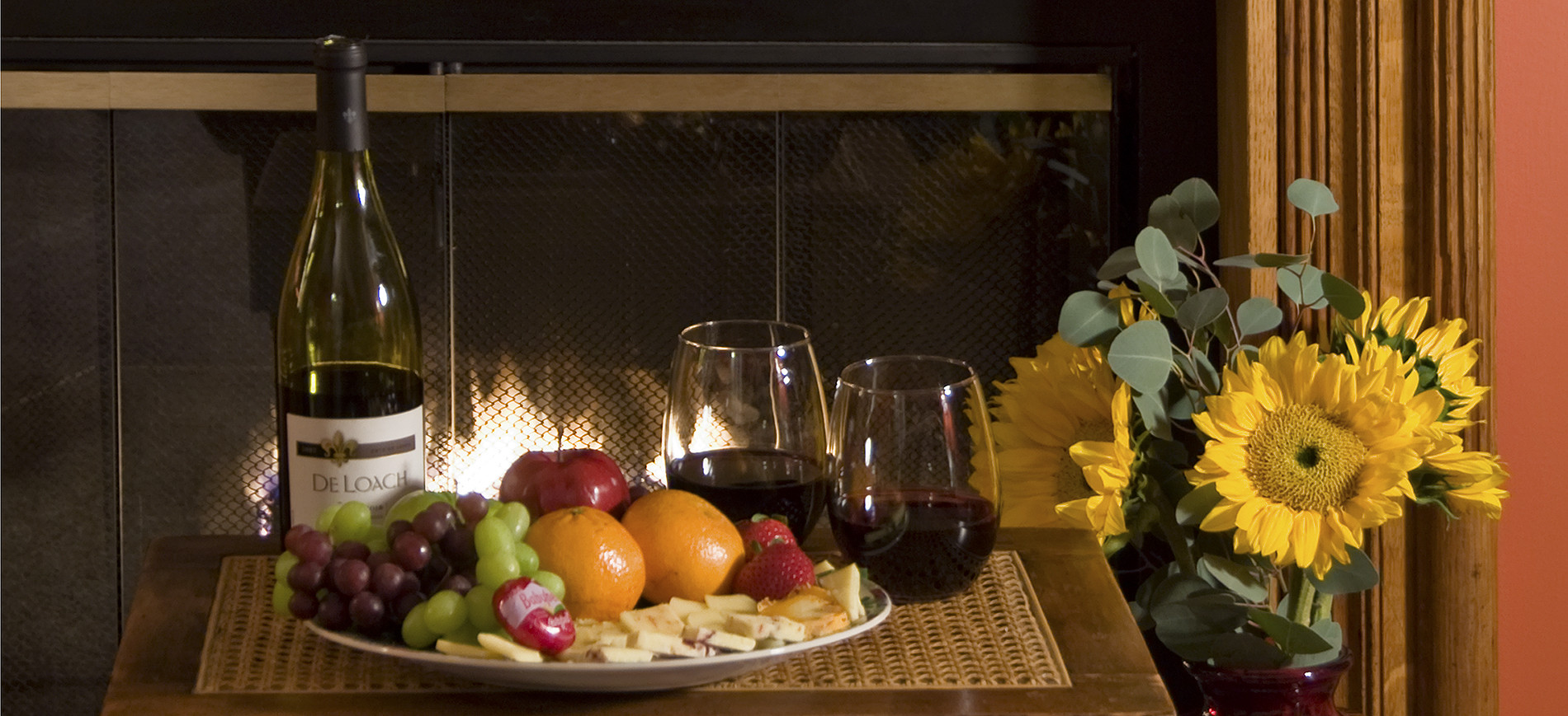 wine bottle, fruit & cheese plate, two glasses wine, sunflowers with fireplace behind