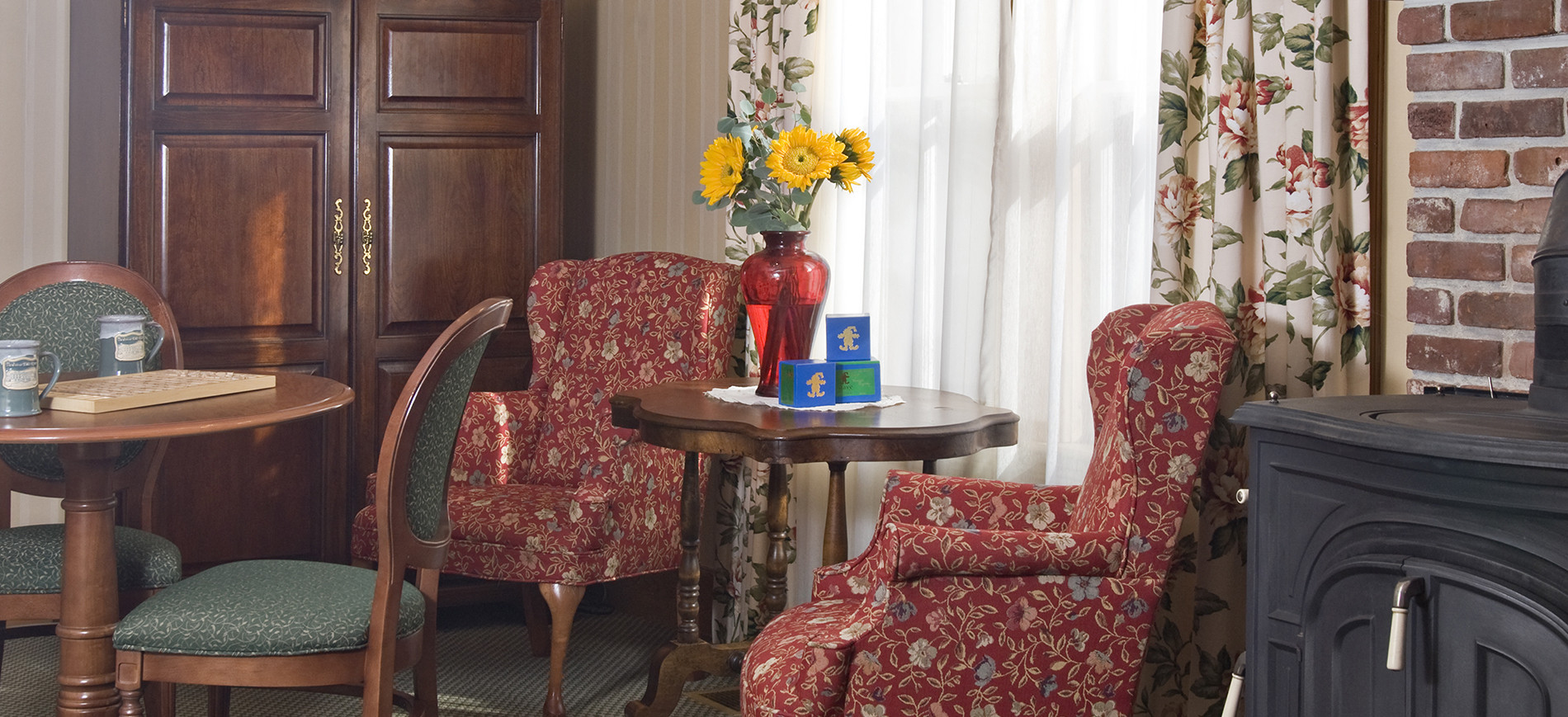 Two wing chairs next to round table with sunflowers in red vaser