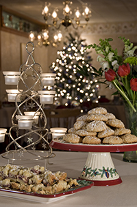 silver & white votive candle stand, tray of cookies, platter of cookies, vase of flowers & Christmas tree in background