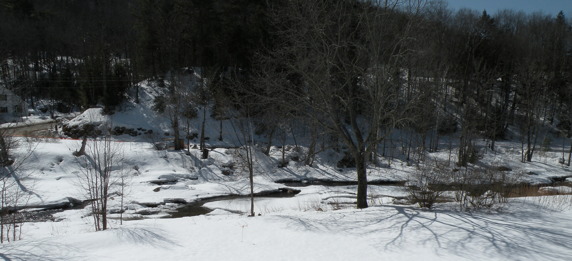 snow along tree lined Ellis River NH in winter