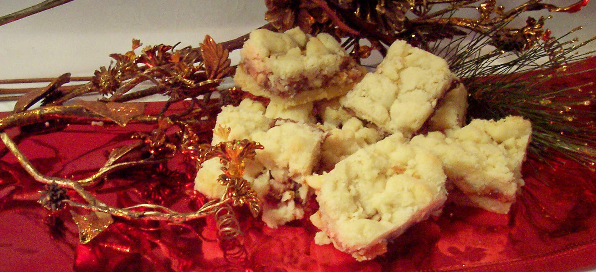 Raspberry Almond Cookie Bars on red ribbon with gold twigs & pinecone in background
