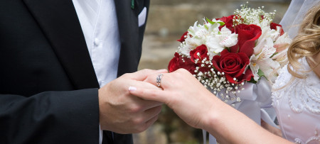 groom & bride holding hands with ring and bouquet