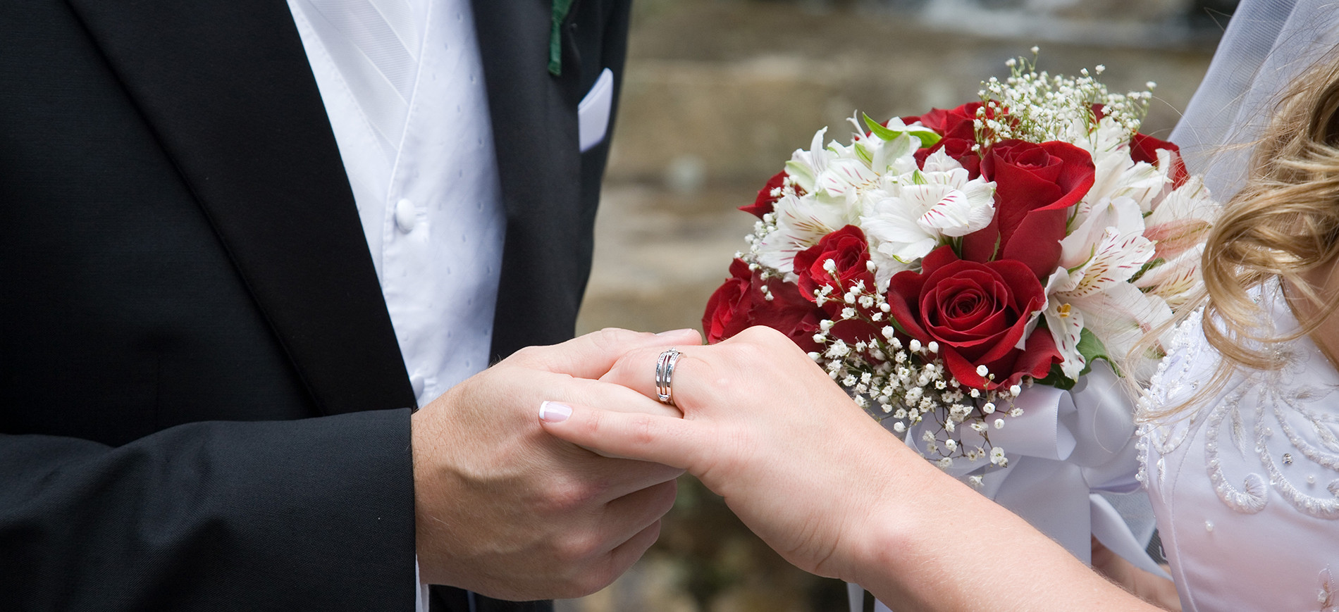 two hands with wedding rings & bouquet