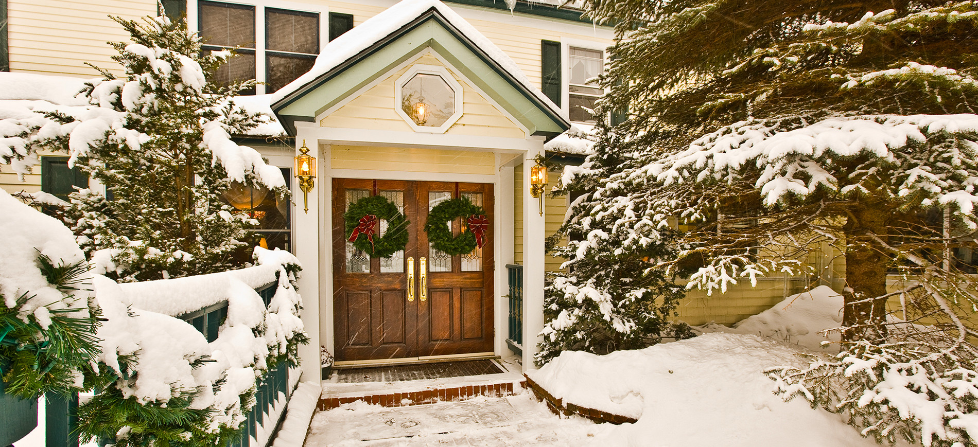 Inn at Ellis River portico & entry doors with wreaths in snow