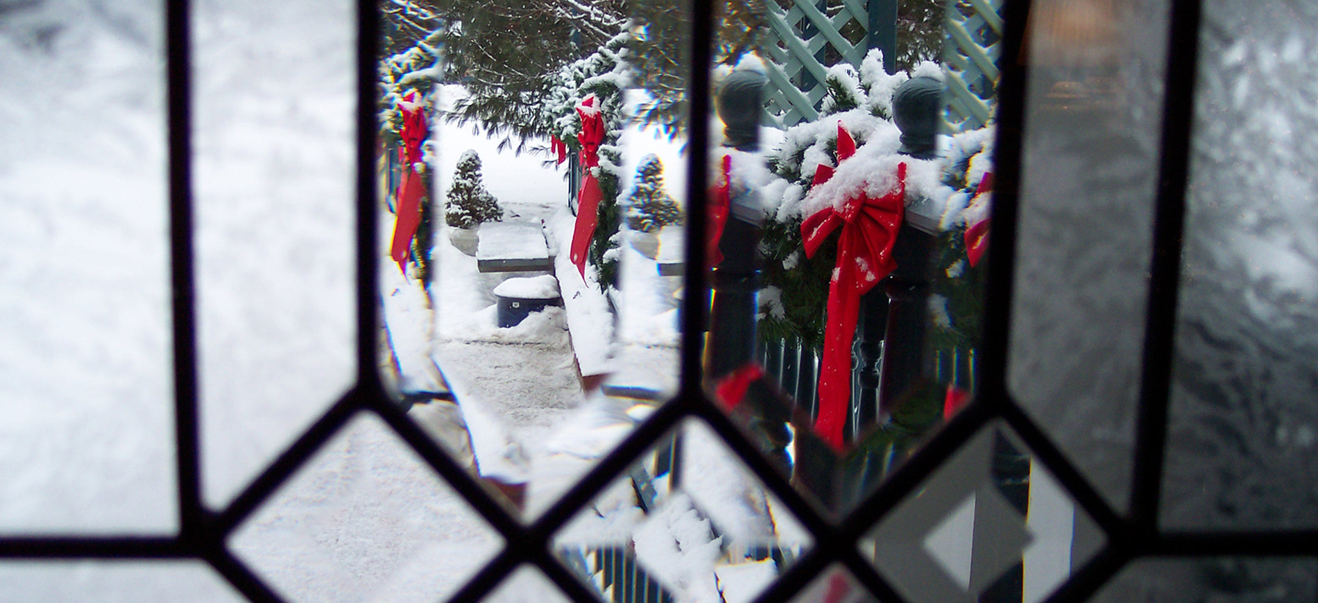 Clear stained glass with view of evergreen roping & red bows in snow outside