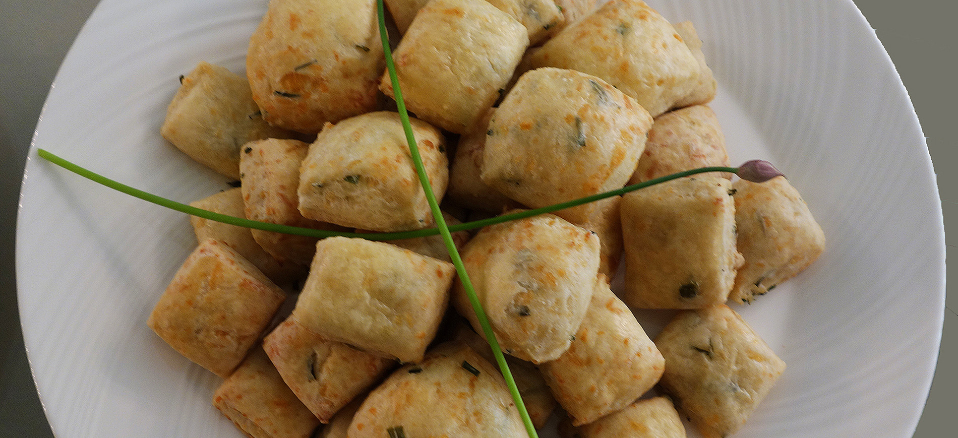 Italian Cheese Biscuits on white plate with chive garnish