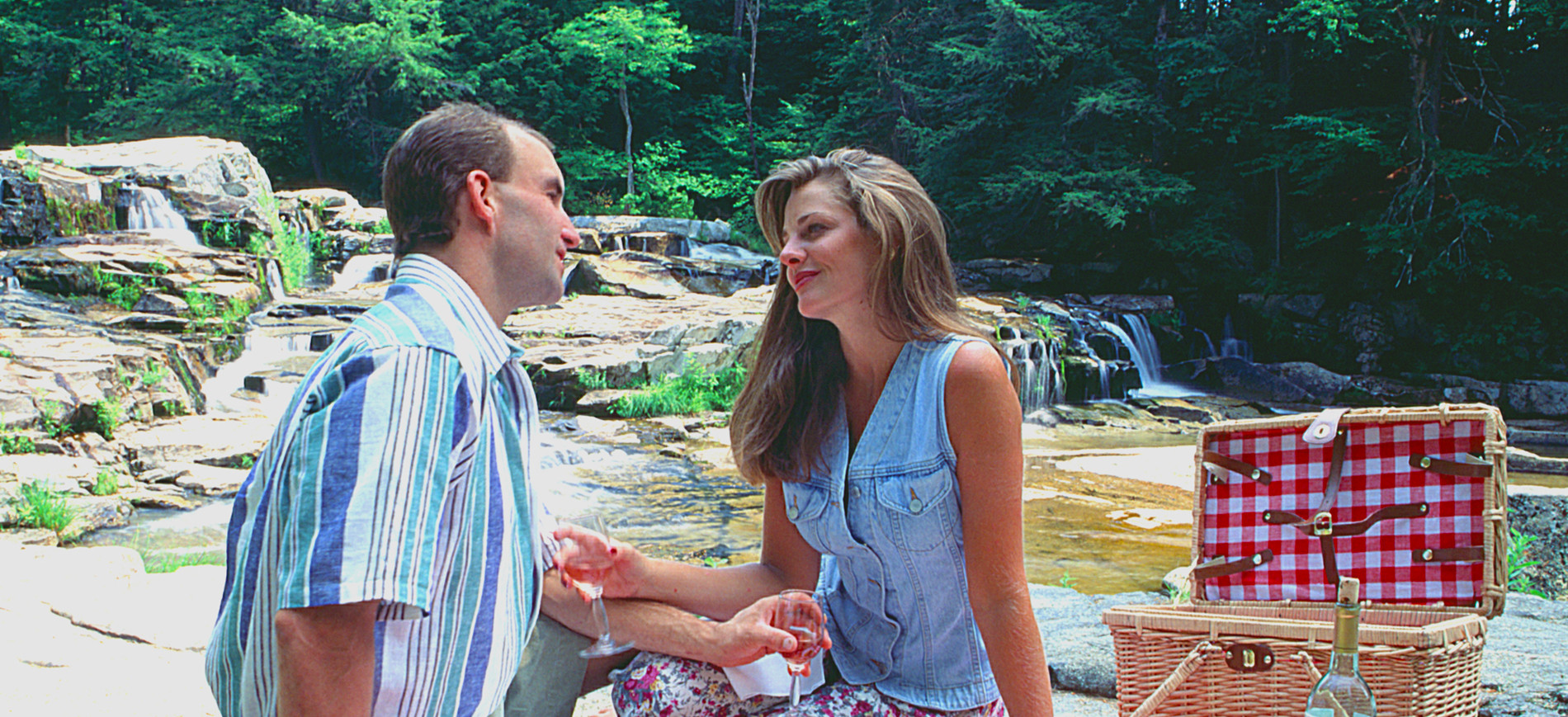 Couple toasting at picnic lunch by waterfall