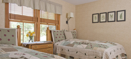 Guest room with two double beds with tan & green quilts, window and oak dresser with flowers between beds, four fern prints on wall behind bed