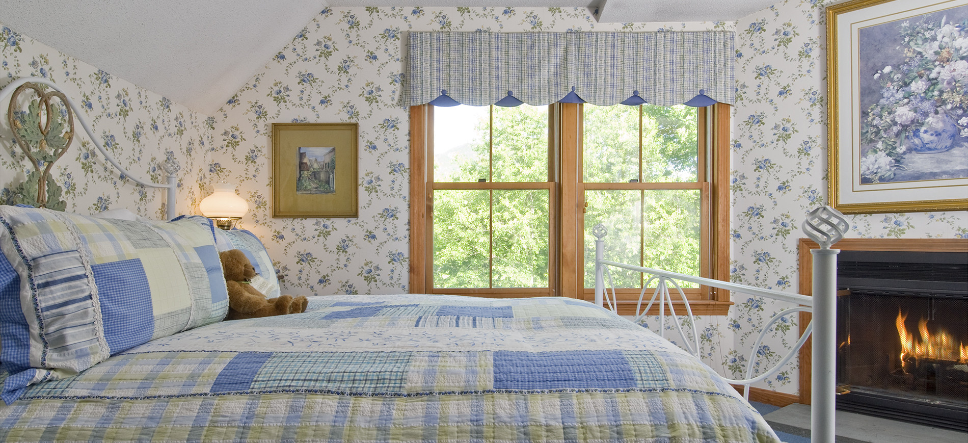 Guest room with king white iron bed & blue plaid bedding, blue & white wallpaper, window with plaid valence, fireplace with picture above