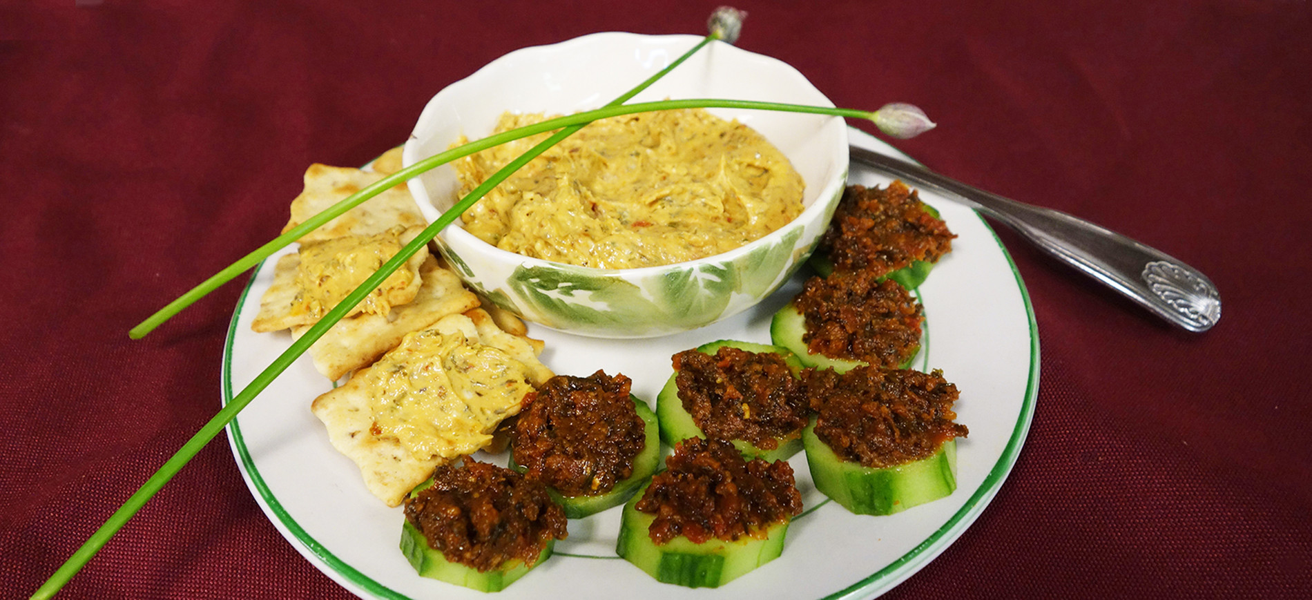 Sun dried tomato pesto on cucumber rounds, pesto dip in bowl and on crackers