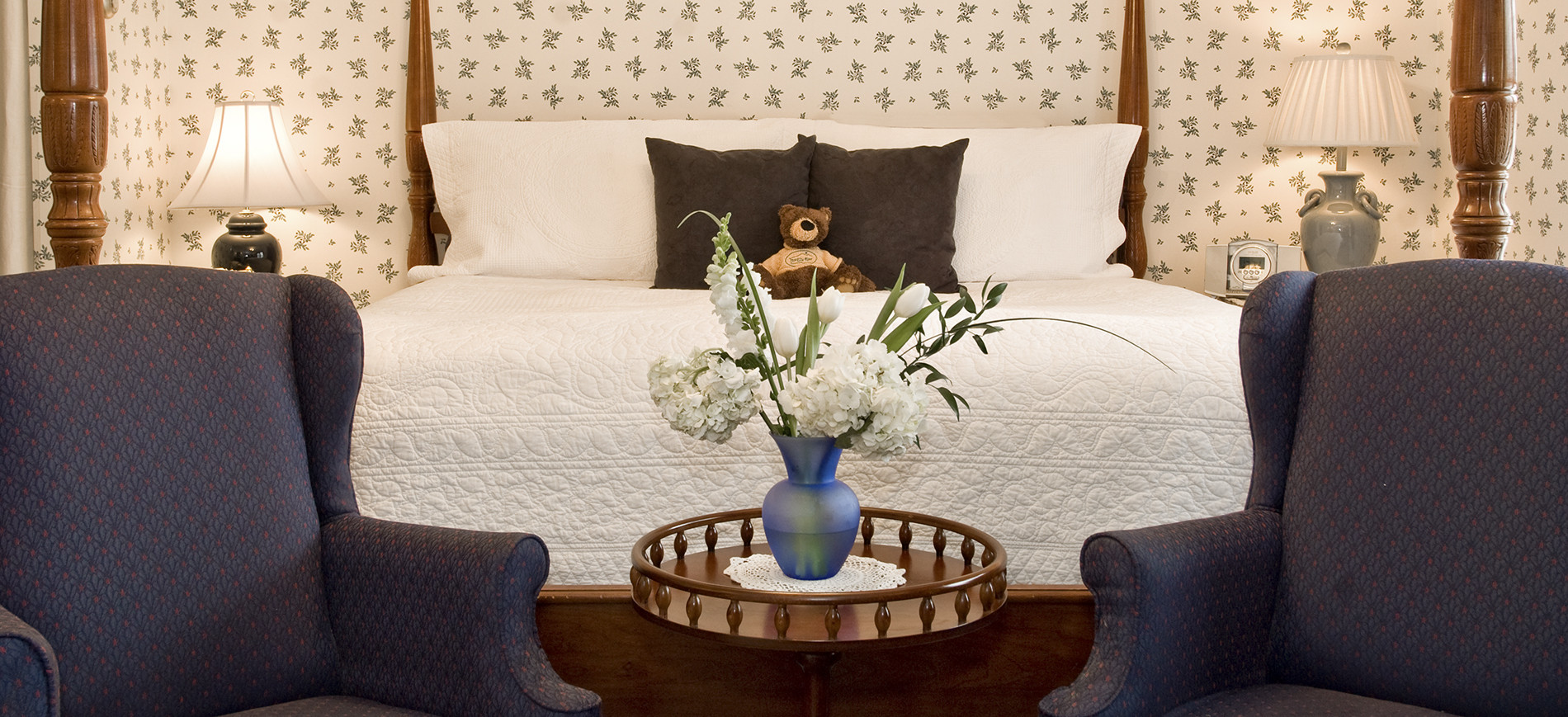 Guest room with white & blue wallpaper, king bed with white bedding in back of blue wing chairs with round table with flowers