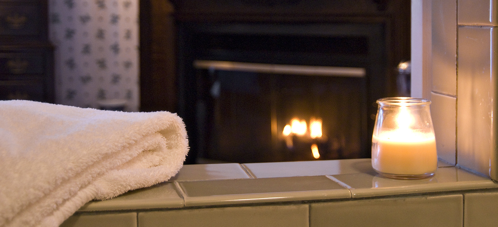 folded towel and candle on jetted tub with fireplace behind