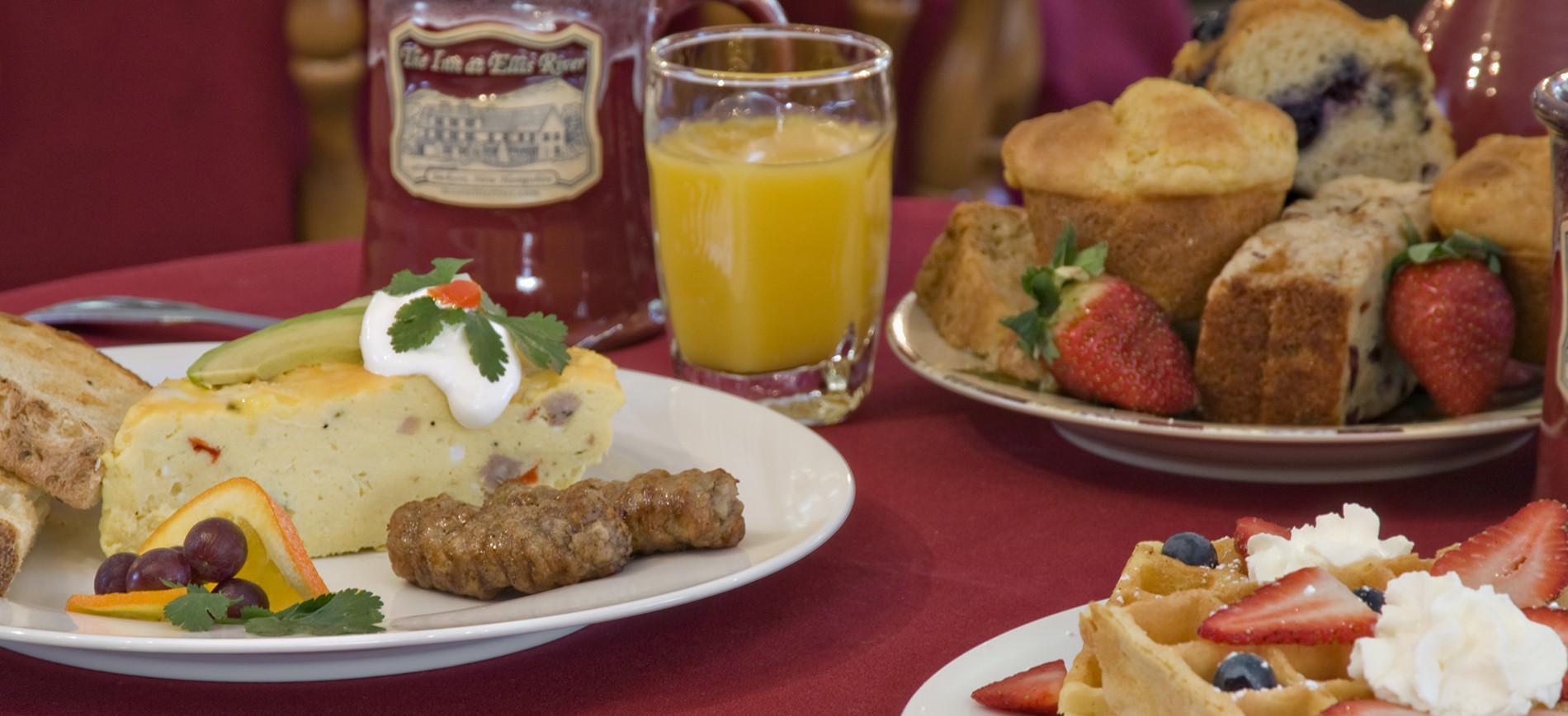 Frittat with sausage & toast on left, mug & orange juice glass, muffins, waffle with strawberry & whipped cream