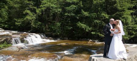 Bride & groom on rock by waterfall