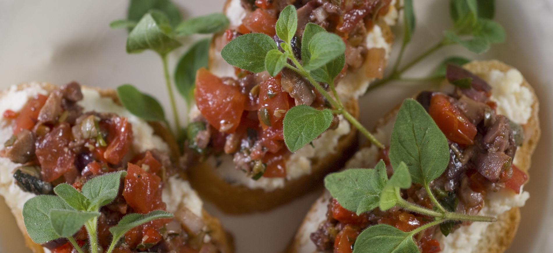 Three pieces of bruschetta topped with chopped tomato & oregano garnish