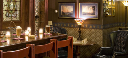 Bar with drinks & bar stools, chess set, lamp, pictures in background