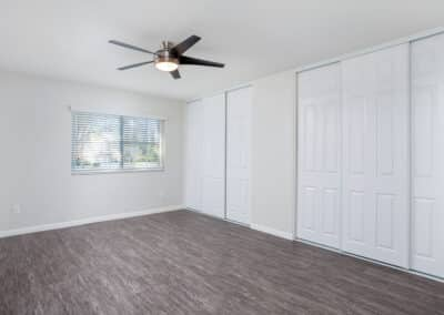 Master bedroom with ceiling fan, window, and closet space
