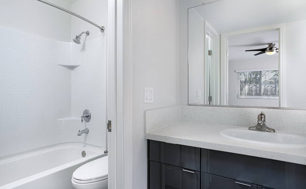 white bathroom showing the sink, bathtub, and cabinets
