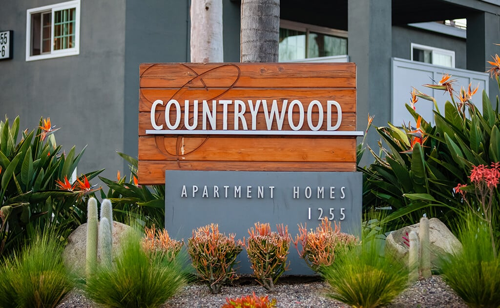 Countrywood Apartment Homes sign with plants