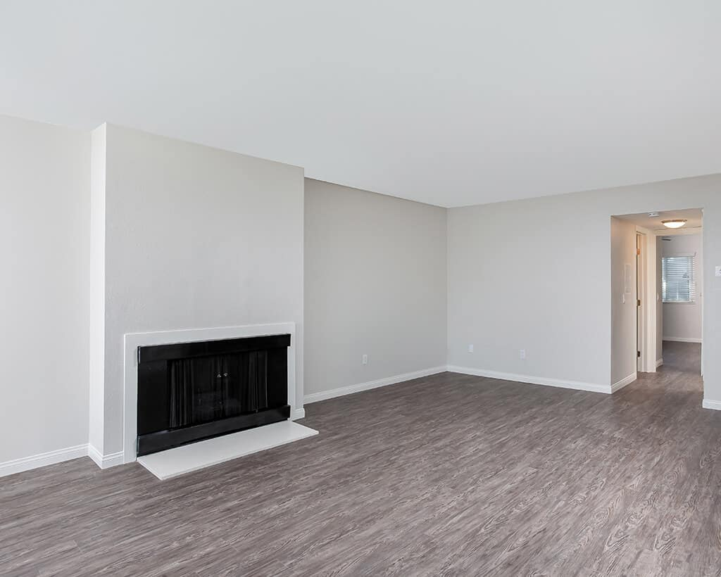 Empty living room with fireplace and wood flooring
