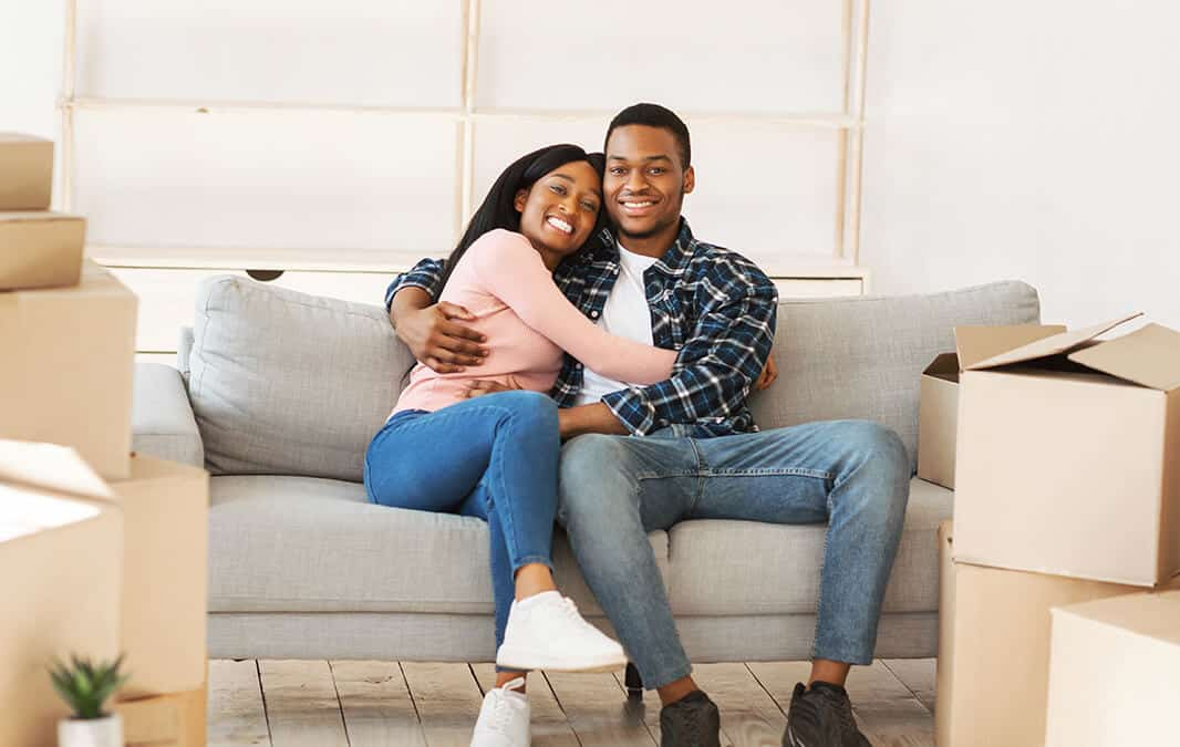 couple sitting on couch in new home