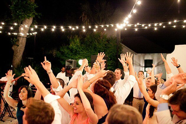 people listening to a dj at a wedding
