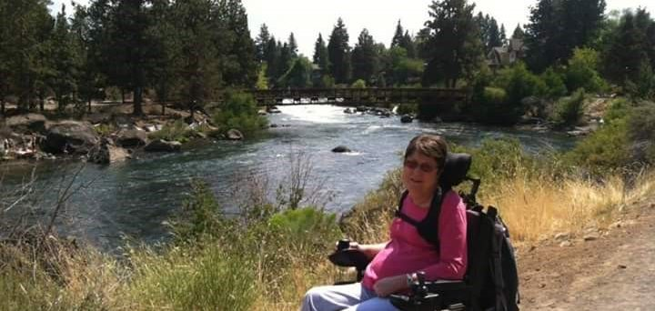 Shelley P. seated in her wheelchair in front of a stream near a forest.