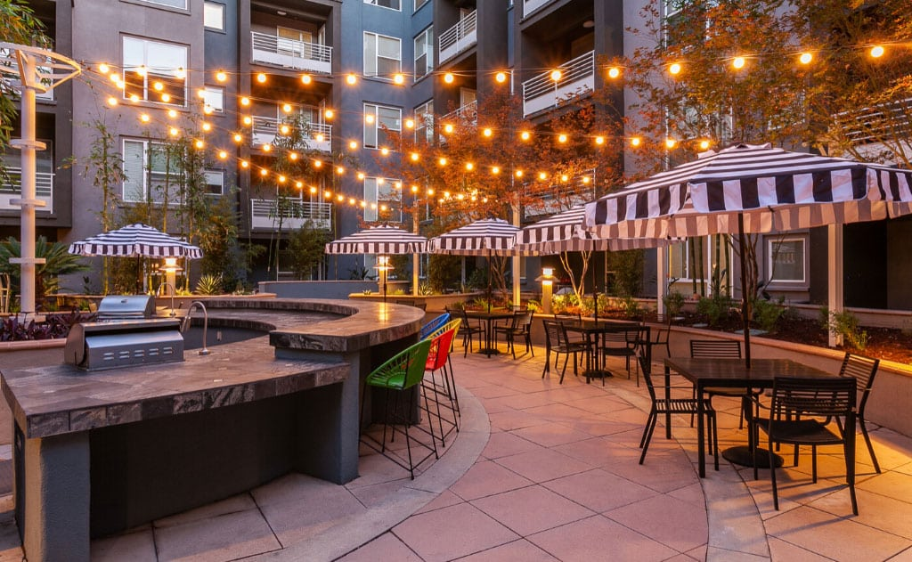 BBQ grills and outdoor bar areas with string lights and seating