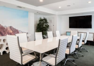conference room with white table and chairs with tv on the wall