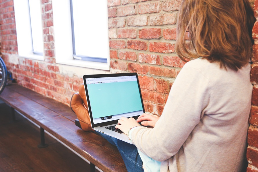Woman on laptop against a brick wall
