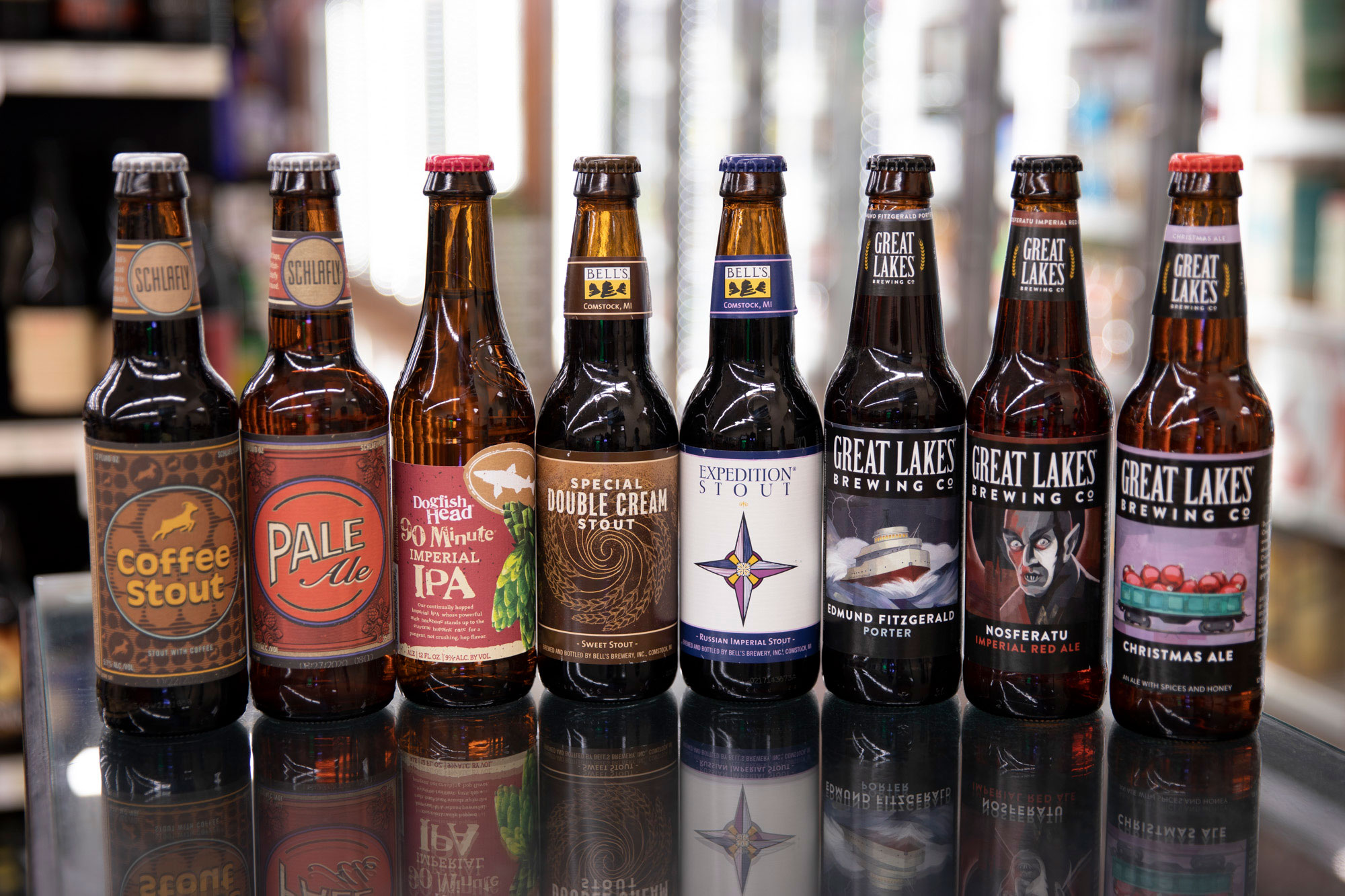 various types of craft beer bottles lined up in a row
