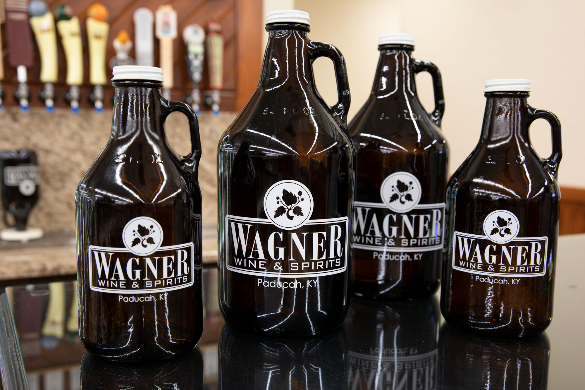 Wagners growlers lined up in front of the craft beer taps