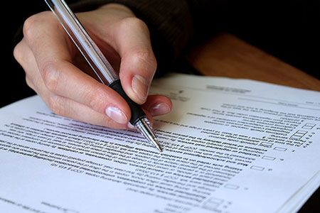 Photo of banking legal document being signed with a pen